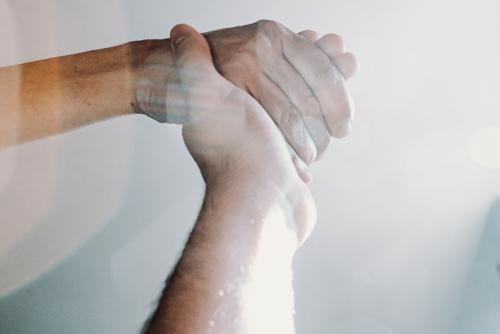 Deux mains qui se tiennent l'une et l'autre : image d'entraide