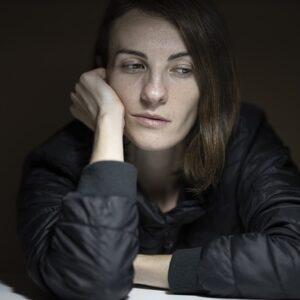 Une femme déprimée accôtant la tête sur son bras